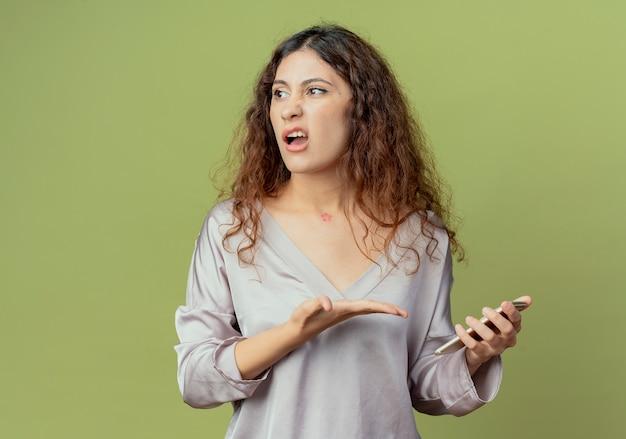 Kijkend naar kant verwarde jonge mooie vrouwelijke kantoormedewerker bedrijf en punten met hand naar telefoon geïsoleerd op olijfgroene muur