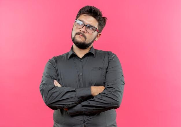 Kijkend naar kant verwarde jonge zakenman die glazen draagt die handen kruisen die op roze muur worden geïsoleerd