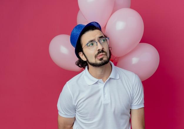 Kijkend naar kant verwarde knappe man met bril en blauwe hoed staande voor ballonnen geïsoleerd op roze muur