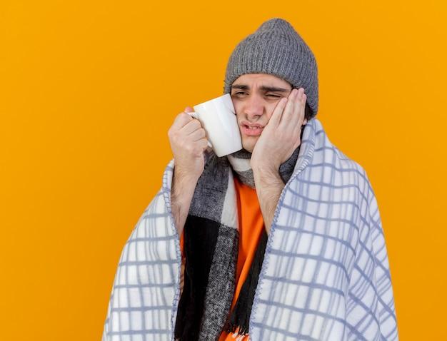 Kijkend naar kant zwakke jonge zieke man met winter hoed met sjaal gewikkeld in geruite hand zetten