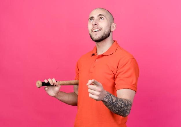 Kijkend naar lachende jonge sportieve man met beisbol bit en toont je gebaar geïsoleerd op roze muur