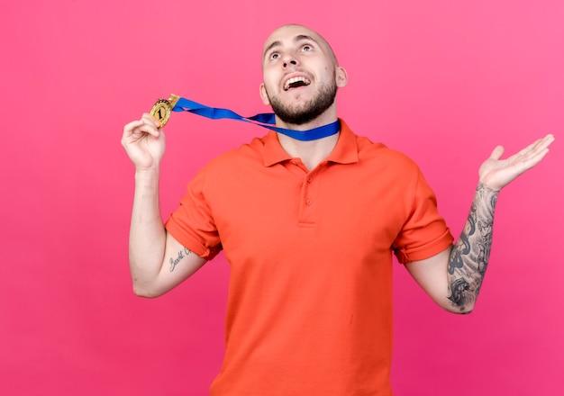 Kijkend naar lachende jonge sportieve man met medaille en hand vast te houden en uit te spreiden