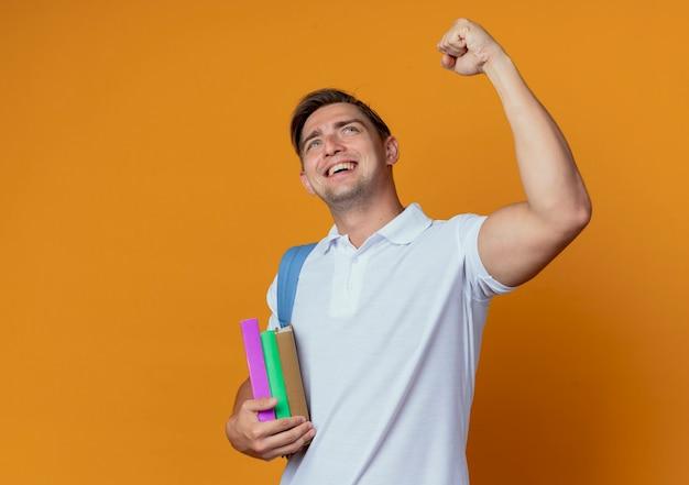 Kijkend naar omhoog blije jonge knappe mannelijke student die rugtas draagt die vuist opheft die op oranje muur wordt geïsoleerd