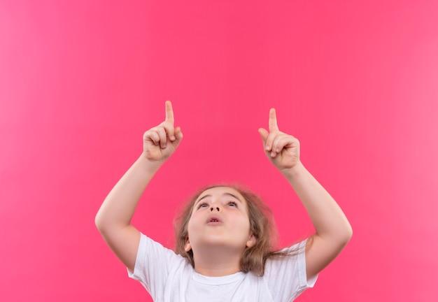 Kijkend naar omhoog wijst klein schoolmeisje dat een wit t-shirt draagt omhoog op geïsoleerde roze achtergrond
