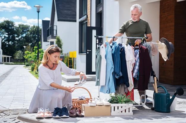 Kijkend naar schoenen. aantrekkelijk blonde-haired vrouw die gestreepte kleding draagt die schoenen bekijkt bij werfverkoop die het met echtgenoot bezoekt