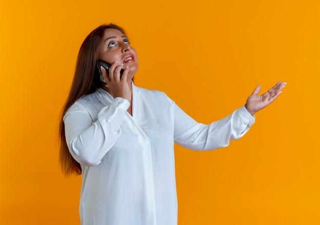 Kijkend naar tevreden casual blanke vrouw van middelbare leeftijd spreekt aan de telefoon en spreidt de hand