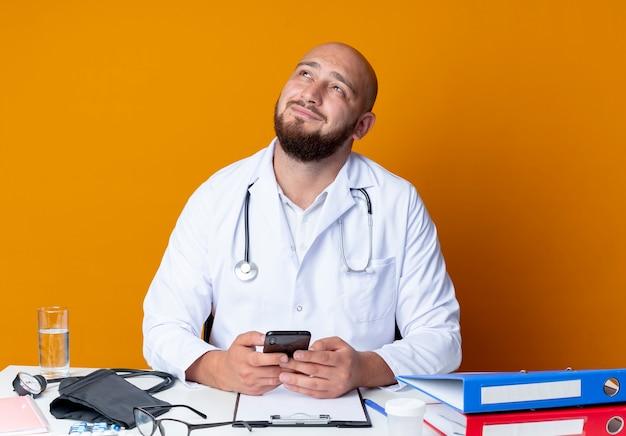 Kijkend naar tevreden jonge kale mannelijke arts die medische gewaad en stethoscoop draagt ?? die aan bureau zit met medische hulpmiddelen die telefoon houden die op oranje achtergrond wordt geïsoleerd