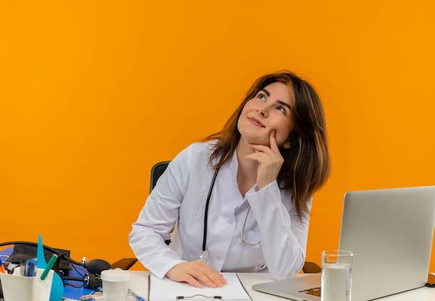 Kijkend naar tevreden vrouwelijke arts van middelbare leeftijd die medische mantel draagt met een stethoscoop zittend aan een bureau werkt op laptop met medische hulpmiddelen hand op de wang op oranje muur zetten