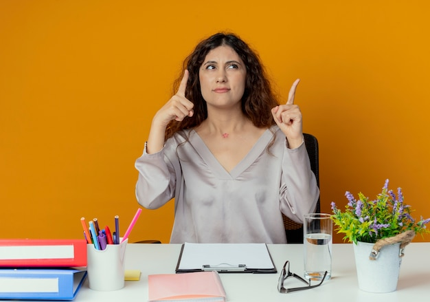 Kijkend naar verwarde jonge, mooie vrouwelijke kantoormedewerker die aan een bureau zit