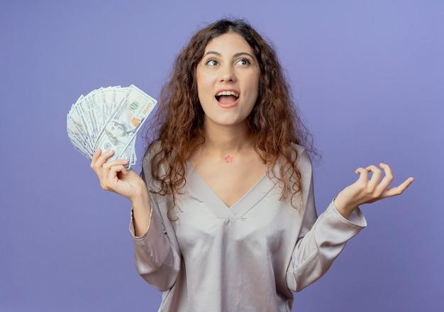Kijkend naar vrolijke jonge mooie meisje met contant geld en spreidde hand