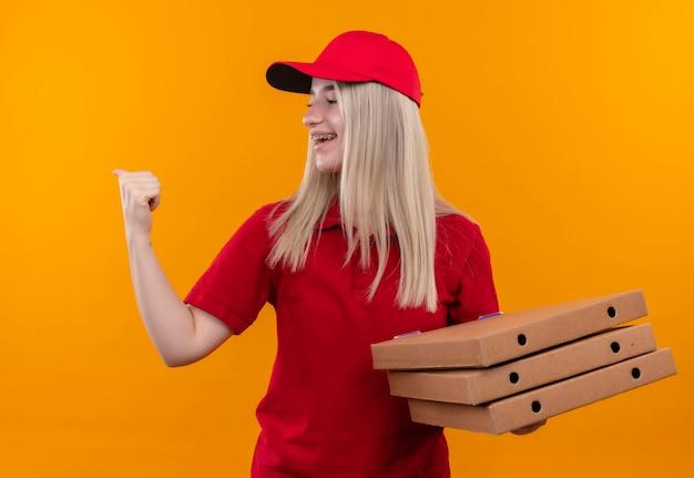 Kijkend naar zijlevering jonge vrouw die rode t-shirt en pet draagt die pizzadoos houdt die ja gebaar op geïsoleerde oranje muur toont