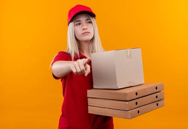 Kijkend naar zijlevering jonge vrouw, gekleed in een rode t-shirt en een pet met pizzadoos wijst naar de zijkant op geïsoleerde oranje muur