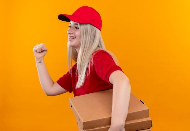 Kijkend naar zijlevering jonge vrouw, gekleed in rode t-shirt en pet in tandsteun met pizzadoos met ja gebaar op geïsoleerde oranje muur
