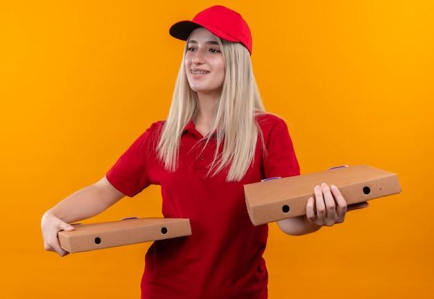 Kijkend naar zijlevering jonge vrouw, gekleed in rode t-shirt en pet in tandsteun met pizzadoos op geïsoleerde oranje muur