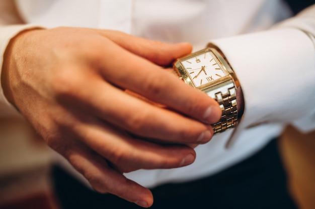 Kijkend op het horloge op zijn hand