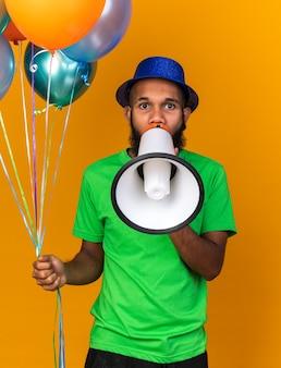 Kijkende camera jonge afro-amerikaanse man met feestmuts met ballonnen spreekt op luidspreker