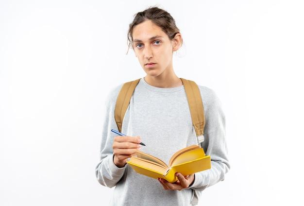 Kijkende camera jonge kerel student draagt rugzak met boek geïsoleerd op een witte muur
