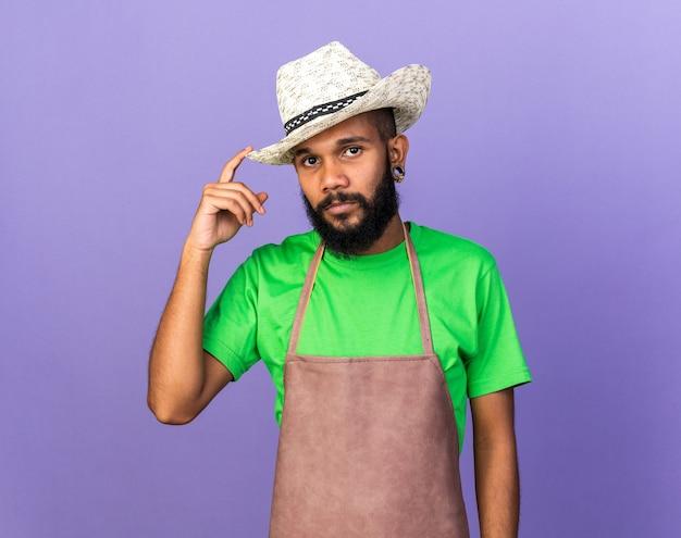 Kijkende camera jonge tuinman afro-amerikaanse man met tuinhoed geïsoleerd op blauwe muur