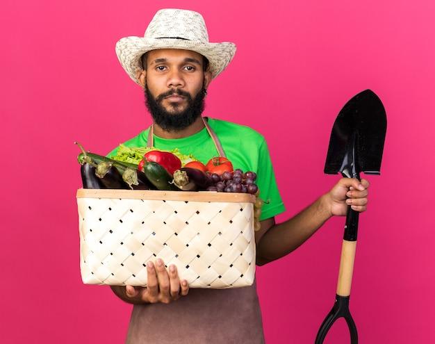 Kijkende camera jonge tuinman afro-amerikaanse man met tuinhoed met groentemand met spade