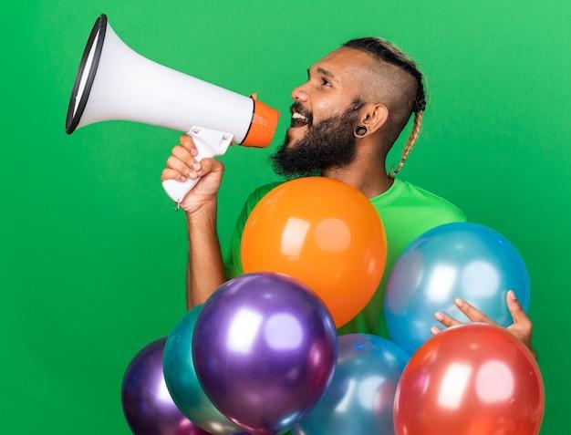 Kijkende jonge afro-amerikaanse man met een groen t-shirt achter ballonnen spreekt op luidspreker geïsoleerd op groene muur