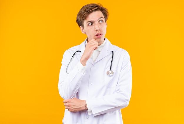 Kijkende jonge mannelijke arts die een medisch gewaad draagt met een stethoscoop die de hand onder de kin legt die op een oranje muur is geïsoleerd