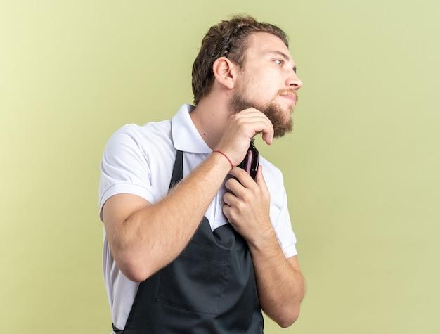 Kijkende jonge mannelijke kapper die een uniforme trimbaard draagt met een tondeuse geïsoleerd op een olijfgroene muur