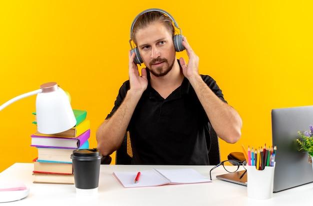 Kijkende jonge student die een koptelefoon draagt die aan tafel zit met schoolgereedschap
