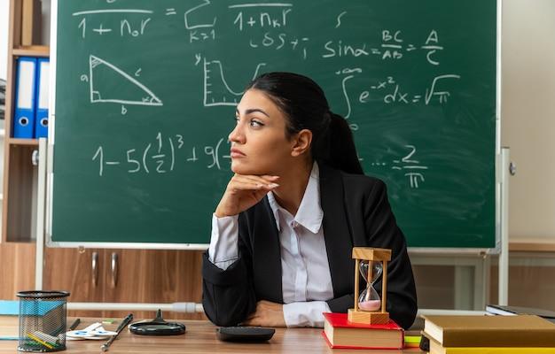 Kijkende jonge vrouwelijke lerares zit aan tafel met schoolspullen en legt hand onder de kin in de klas
