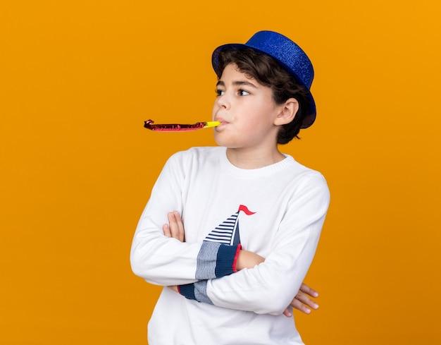 Kijkende kleine jongen met een blauwe feesthoed die een feestfluitje blaast en de handen kruist geïsoleerd op een oranje muur