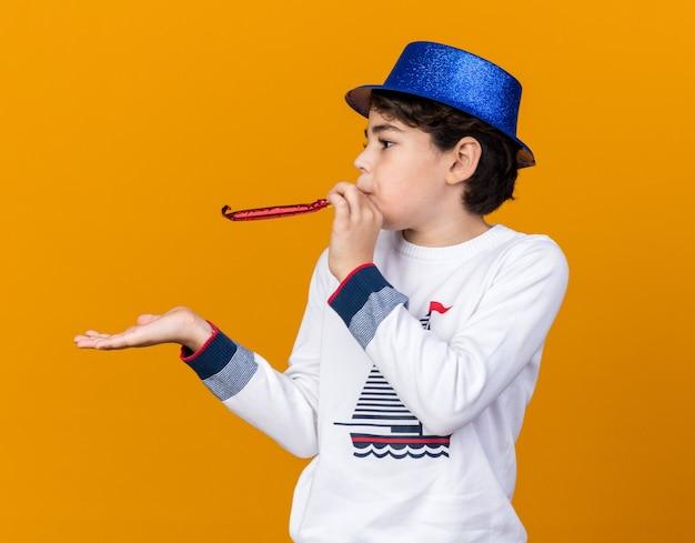Kijkende kleine jongen met een blauwe feestmuts die een feestfluitje blaast dat op een oranje muur wordt geïsoleerd