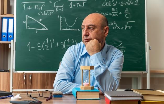 Kijkende mannelijke leraar van middelbare leeftijd zit aan tafel met schoolbenodigdheden in de klas