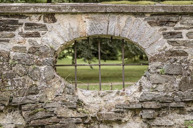 Kijkgat met ijzeren staven op een stenen hek