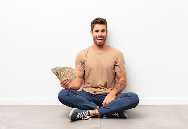 Kijkt blij en aangenaam verrast, opgewonden met een gefascineerde en geschokte uitdrukking die dollarbankbiljetten houdt