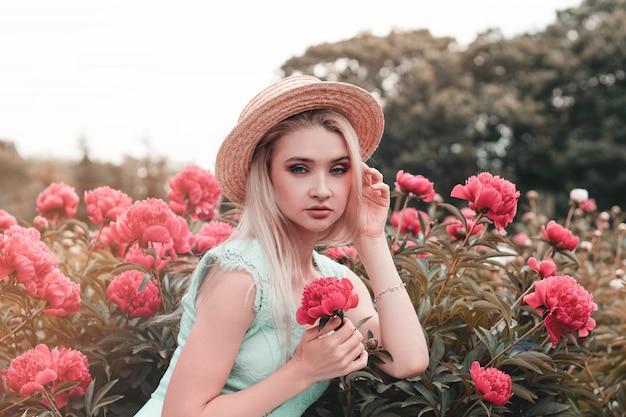 Kijkt de blonde jonge vrouw in roze bloeiende pioenen, meisje het kader