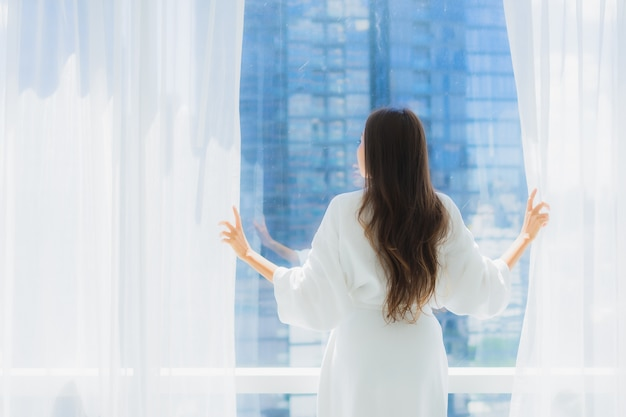Kijkt de mooie jonge aziatische vrouw van het portret buiten venster voor het uitzicht