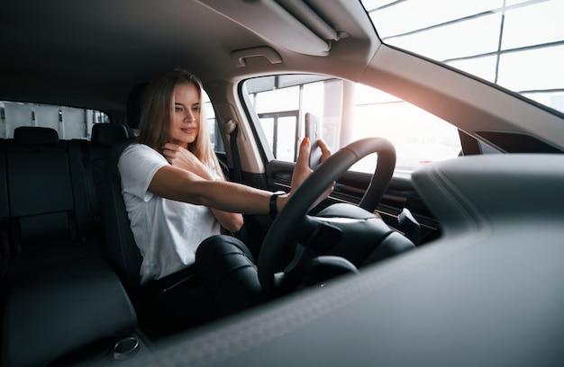 Kijkt naar zichzelf door frontale camera of smartphone te gebruiken. meisje in moderne auto in de salon. overdag binnenshuis. een nieuw voertuig kopen