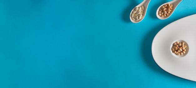 Kikkererwten en bonen op elegante plaat en porseleinen lepels. plat leggen. ruimte kopiëren. snack.