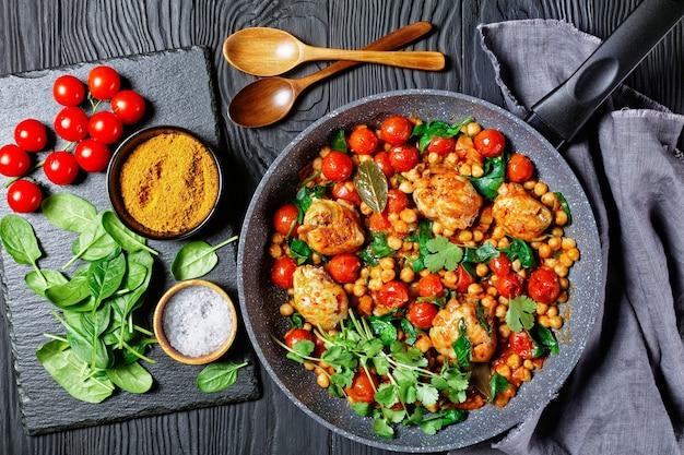 Kikkererwten en kip curry van kippendijen zonder been met cherrytomaatjes en baby spinazie op een koekenpan op een zwarte houten achtergrond met ingrediënten op een tafel, bovenaanzicht, close-up