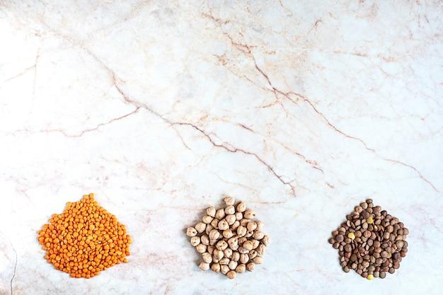 Kikkererwten en twee soorten linzen op een marmeren ondergrond