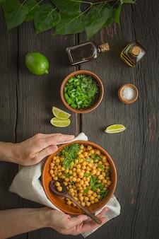 Kikkererwten garneren. vrouw serveert gekookte kikkererwten in een kom op een eettafel. vegetarisch eten