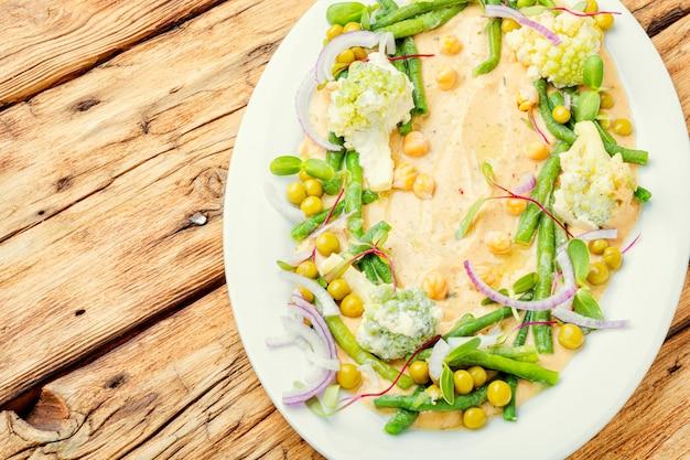 Kikkererwtenhummus met kool, asperges, erwten en microgreens. oosters eten.