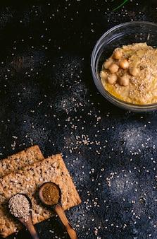 Kikkererwtenhummus met sesam in glaskom op houten lijst. veganistisch eten