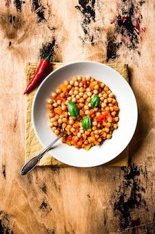 Kikkererwtenstoofpot met tomaat, gele peper en chili, basilicumblaadjes. foto bovenaanzicht, houten oppervlak. schep in een bord.