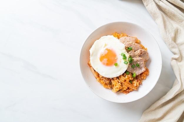 Kimchi gebakken rijst met gebakken ei en varkensvlees. koreaanse eetstijl
