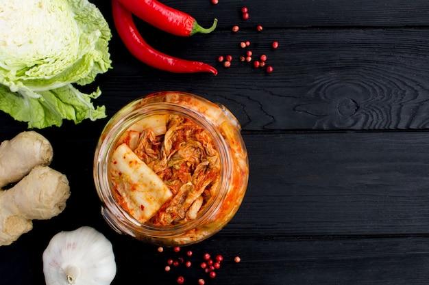 Kimchi in de glazen pot en ingrediënten op de zwarte houten achtergrond. bovenaanzicht. kopieer ruimte.