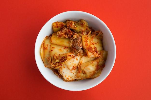Kimchi in de witte plaat op de rode achtergrond. bovenaanzicht. kopieer ruimte.