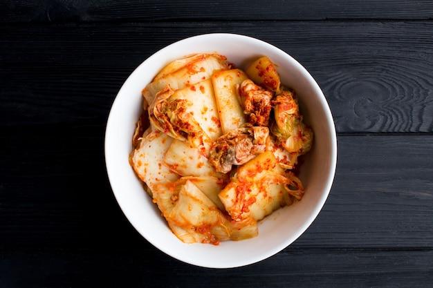 Kimchi in de witte plaat op de zwarte houten achtergrond. bovenaanzicht. kopieer ruimte.