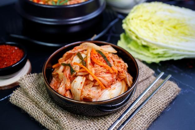 Kimchi kool en rijst eten in een zwarte kom met stokjes.