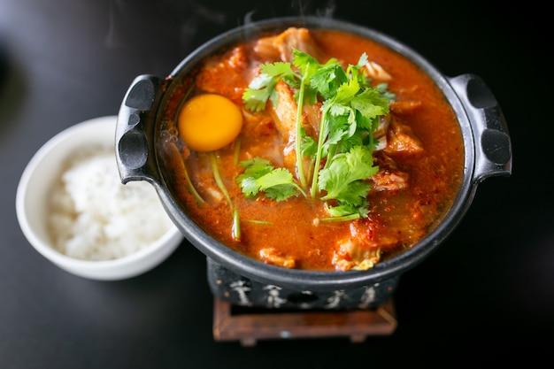 Kimchi-soep met rauwe kippeneieren en witte tofu, populair koreaans eten.