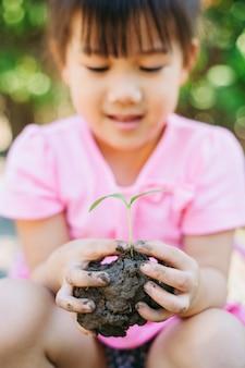 Kind aanplant van een boom voor moeder aarde dag concept.
